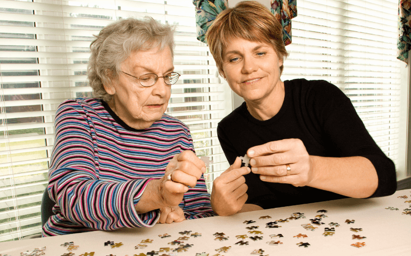 image shows a woman giving elderly care by helping a lady with a jigsaw
