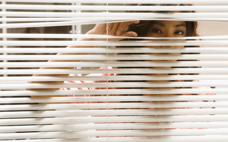 image shows a woman peeping though her blinds