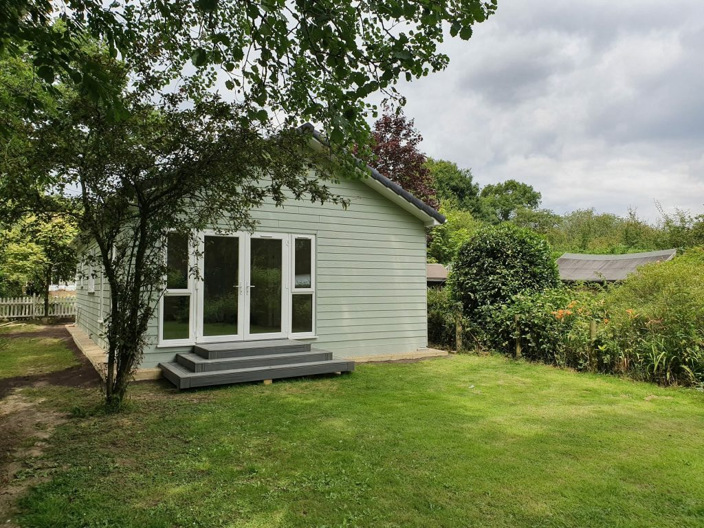 image shows a granny annexe clad in green weatherboard